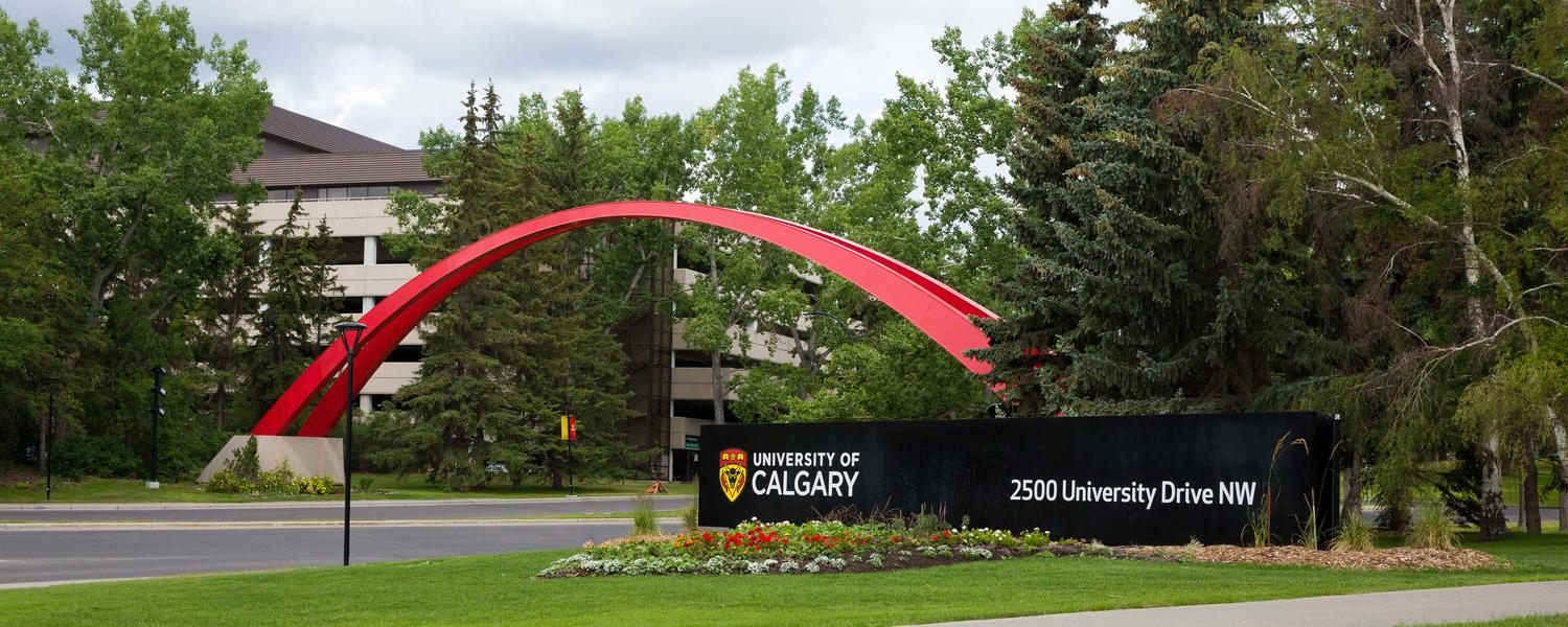 UCalgary main entrance to parking lot 1 and bus loop. Red arch, University of Calgary address on black sign