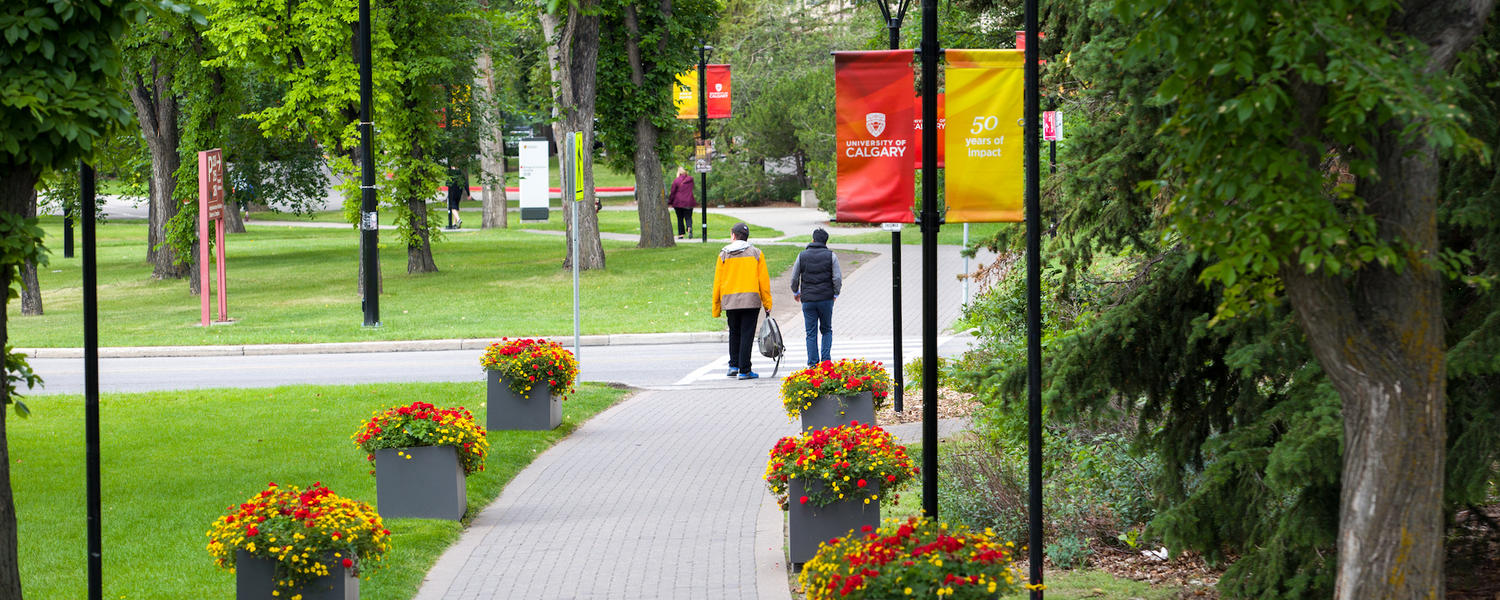 student crossing the street on campus in the summer