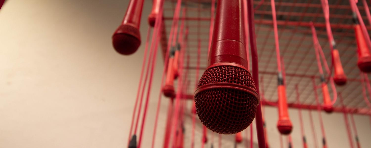 red microphones hang from the ceiling.
