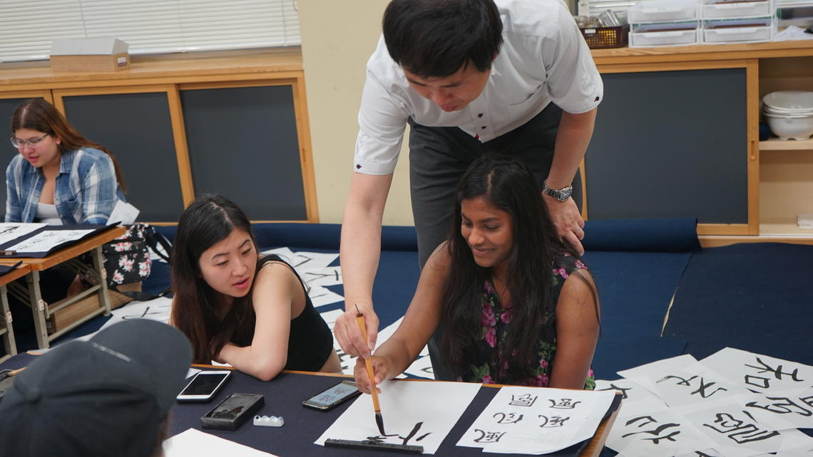 image of students painting Japanese characters