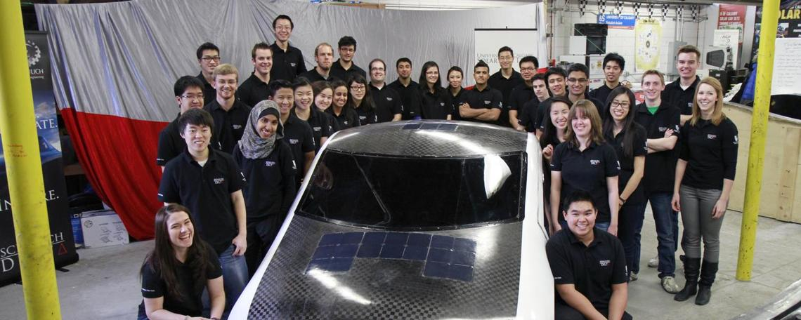 Students pose with solar car
