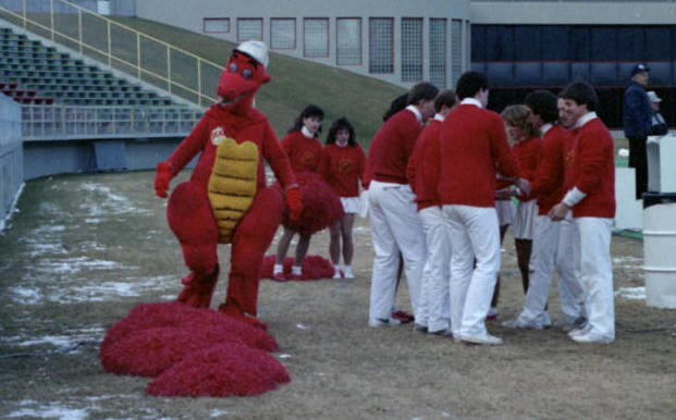 Dexter, the University of Calgary Dinosaurs mascot with the university cheerleading team during a football game.