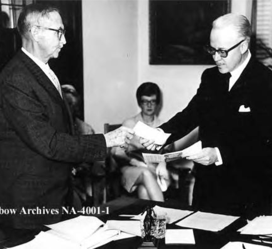 First meeting of new Glenbow Museum organization, took place in old Courthouse on 7th Avenue SW. Eric Harvie, left, handing cheque for $5,000,000 to Honourable Mr. Justice N.D. McDermid, first chairman of the Board of Glenbow governors.