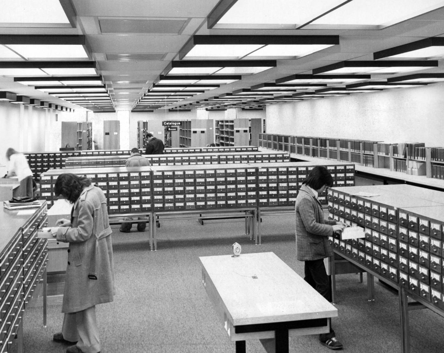 Image of students using the University of Calgary library card catalogue cabinets.