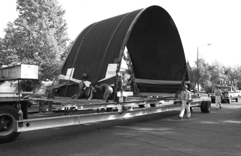 Image of a truck hauling the Olympic Arch, designed by Toronto architect Jack Diamond, to the University of Calgary after it had been on display at city hall following the 1988 Calgary Winter Olympics.