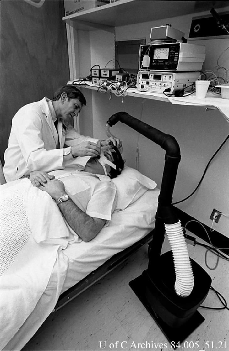 "Heritage Fund researcher, Dr. John Remmers, with a patient wearing a ""sleep mask"" designed by Dr. Remmers, December 1985."