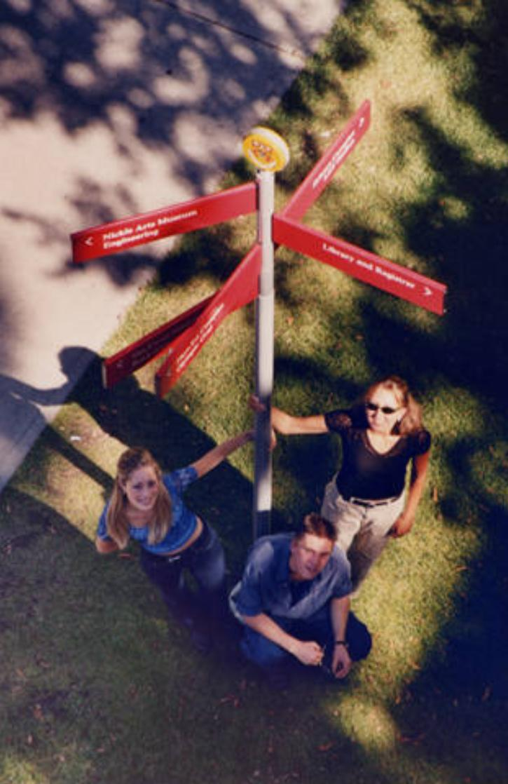 Students outdoors near a campus sign post, 2000.