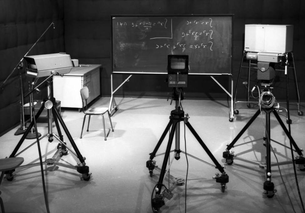A University of Calgary TV studio with video cameras and a blackboard with four equations written on it.
