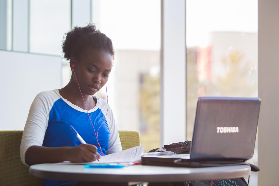 young woman works on a laptop in the library