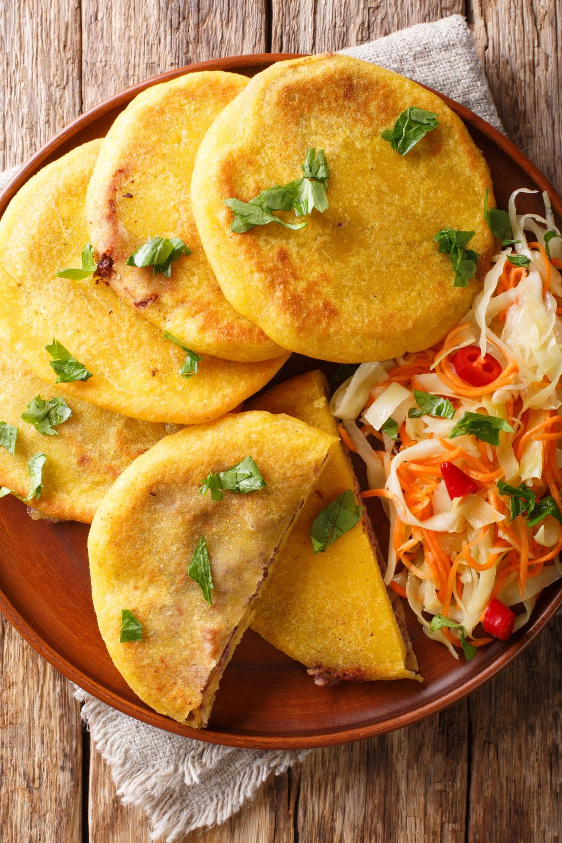 Traditional Latin American pupusas served with curtido closeup on a plate on the table. Vertical top view