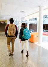 two students walking up a hallway on campus