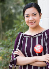 Smiling woman wearing a red Ask Me button
