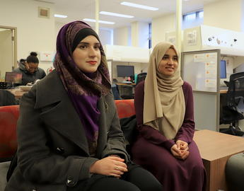 two women wearing hijab sit on a couch