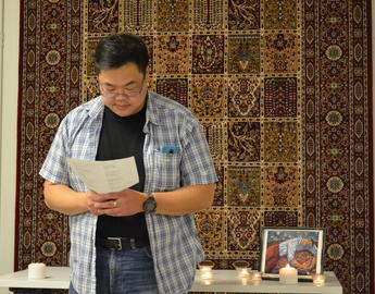 a man wearing a plaid shirt reads from a book