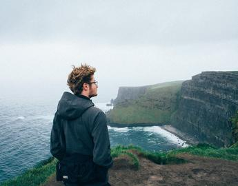 Image of student standing along cliffs of Scotland