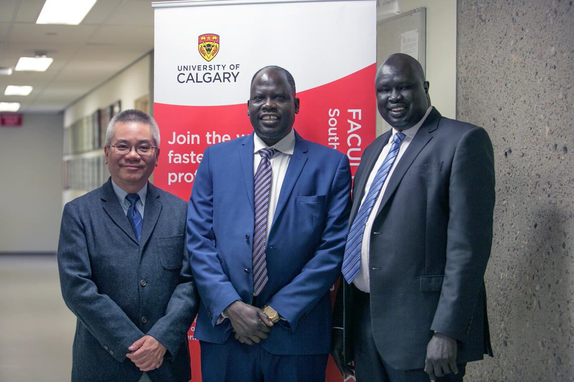 Samuel Mathon, centre, and John Manyok, right, survived war and deprivation to come to Canada, learn English, and graduate from the University of Calgary as social workers. With them is Dr. Siu Ming Kwok, associate dean of the Faculty of Social Work's Southern Alberta Region.