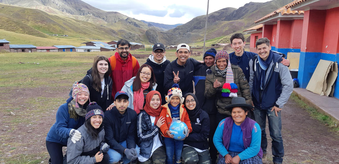 Engineering students pose with villagers in Peru
