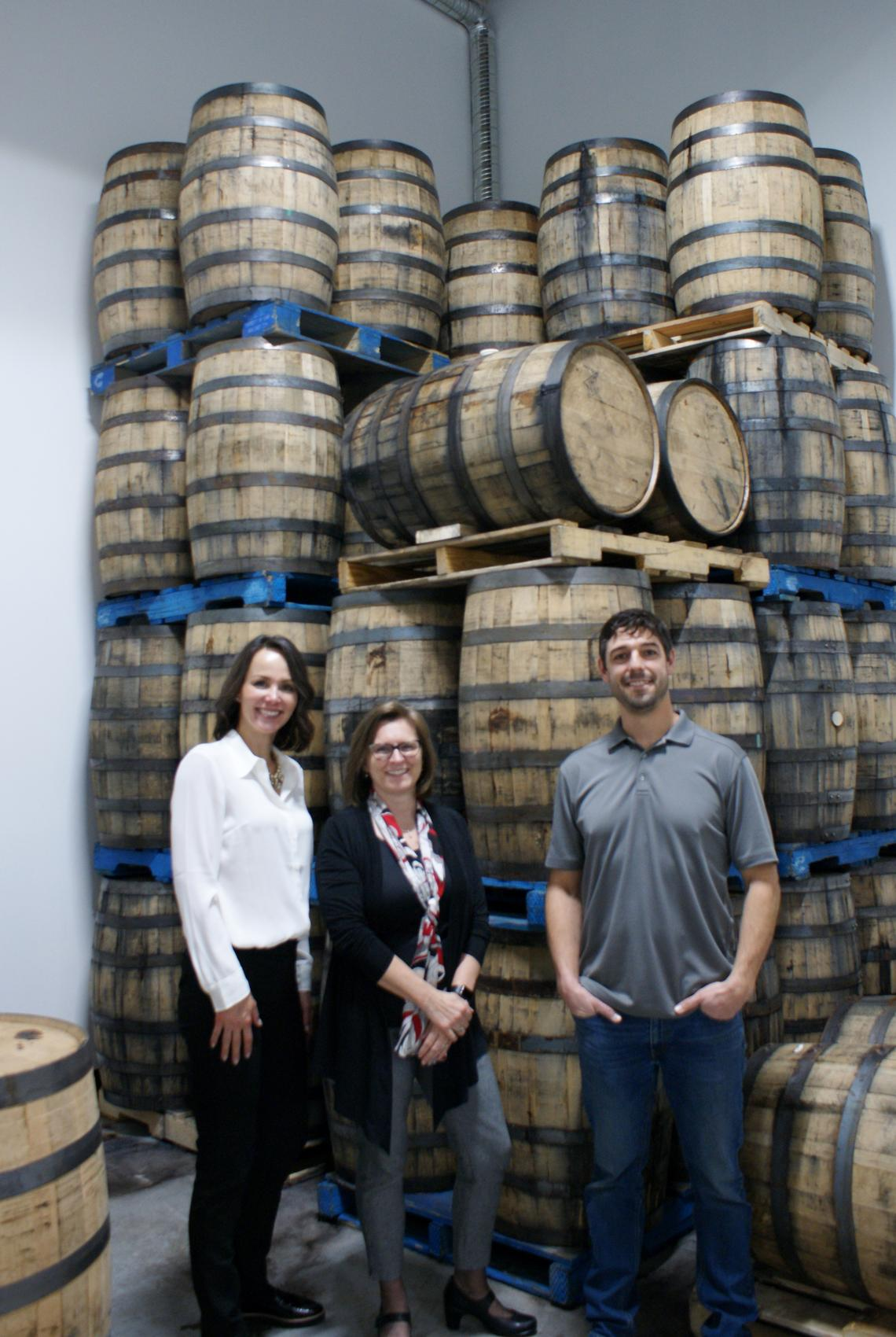 Leitha Cosentino, Director of Development, and Dr. Lesley Rigg, dean of the Faculty of Science, and Tomas Romero, pictured in front of casks at Romero Distilling.