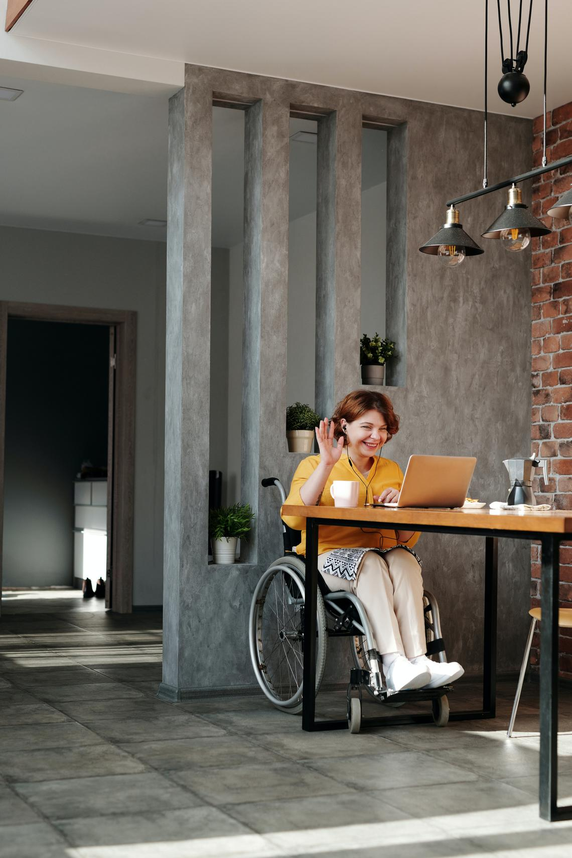 A woman in a wheelchair waving at computer screen
