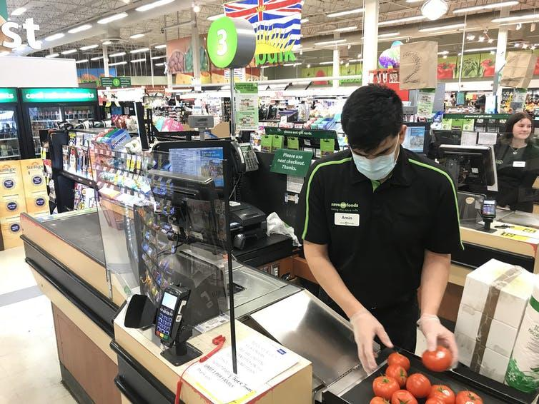 A Plexiglas barrier protects a cashier at a grocery store in North Vancouver, B.C., in March 2020