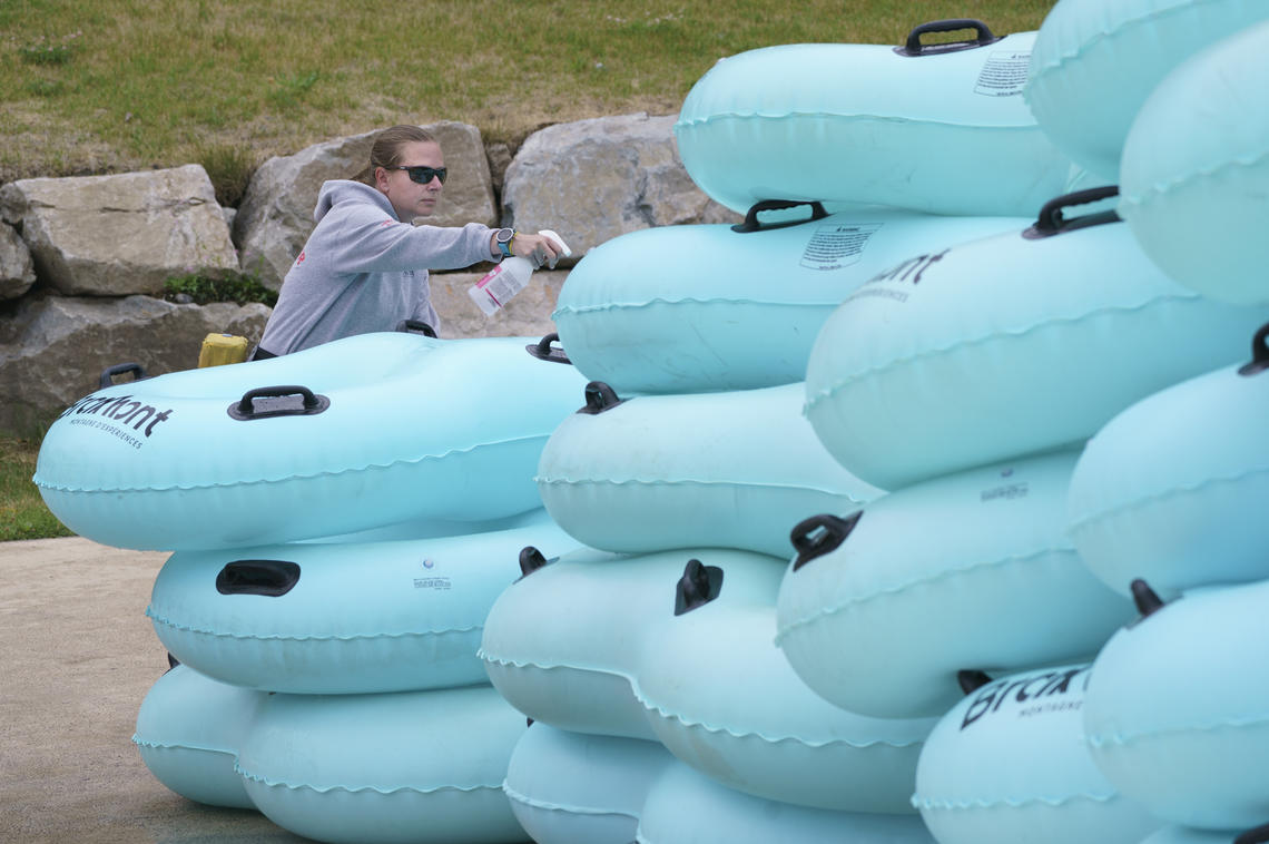 A lifeguard disinfects mattresses used to slide down a water slide in Bromont, Que., in June 2020 as water parks reopened in the province.