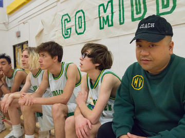A basketball team sitting on a bench
