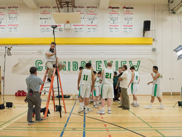 A basketball team and a film crew in a gymnasium