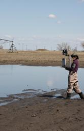 UCalgary hydrology grad student Alex Hughes wades through the mud to download water measurements to her laptop at a GRIP field site in a pond, or depression, in a farmer's field outside of Lethbridge on April 23.
