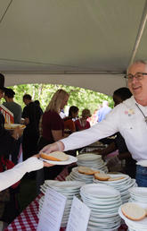 President Ed McCauley serves up barbecue at the annual President's Stampede Barbecue on July 3.