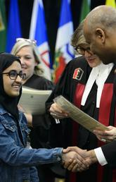 Youth receives Certificate of Citizenship from Immigration Minister