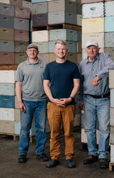 Three men stand in front of palettes of honey