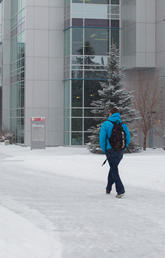 Two people walk in the snow on main campus