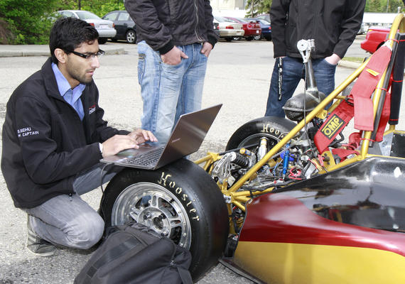 Person working on computer beside a prototype vehicle