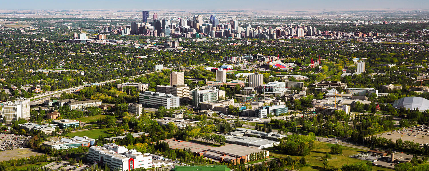 An aerial view of main campus, the research park, and McMahon Stadium in the Calgary landscape, with the downtown skyline in the background.