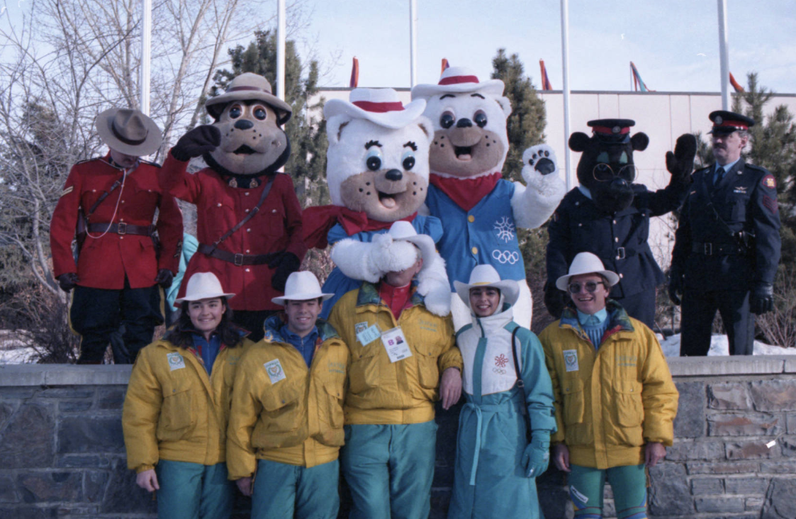 Image of Cypriot Olympic athletes with the 1988 Calgary Winter Olympic mascots Hidy and Howdy during the official ceremony to welcome athletes to the Olympic Village at the University of Calgary.