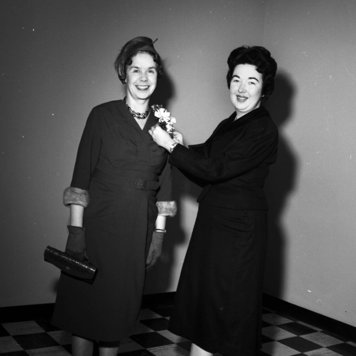 Image of Ethel M. King, advisor to women students and assistant professor of education, right, arranging a gift corsage for Phyllis Ford, wife of Chief Justice Clinton J. Ford, before the ceremonies to open the Arts and Education building.
